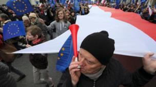 "A man blows a horn during a march called ""I love Europe"" to celebrate the 60th anniversary of the Treaty of Rome in Warsaw, Poland March 25, 2017"
