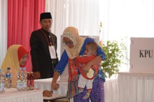 Seorang pemilih, sambil menggendong anaknya, mencelupkan jarinya ke dalam tinta sebagai tanda telah memberikan hak suaranya