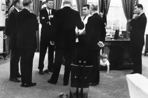 President Kennedy meets with advisors in the Oval Office, while his son, John Jr. plays under the desk. 1963