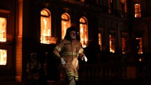 A firefighter walks in front of the National Museum of Rio de Janeiro, one of the oldest in Brazil, as it is consumed by flames due to a major fire, in Rio de Janeiro, Brazil, 2 September 2018.