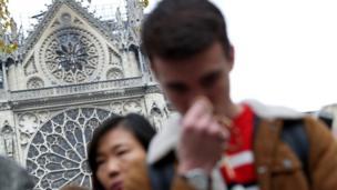 Personas rezan frente a Notre Dame