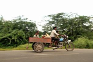 બાઇકની પાછળ ટ્રોલીમાં બેસીને રસ્તા પર જતો પરિવાર