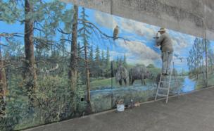 A man paints a mural onto a concrete wall
