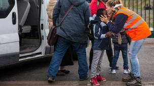 Un geste d'amour... une humanitaire rassure un enfant avant qu'il prenne le bus