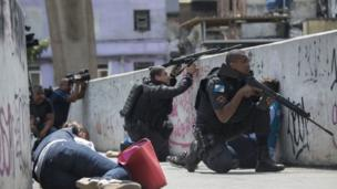 Policemen and journalists take cover during an operation to fight heavily armed drug traffickers at the Rocinha favela in Rio de Janeiro, Brazil, on September 22, 2017.