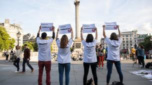 """People hold up signs saying """"Turn to Love for Manchester"""" during a vigil in Trafalgar Square, London"""