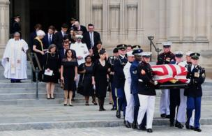 A military honour guard and the McCain family accompany the casket down the Cathedral steps