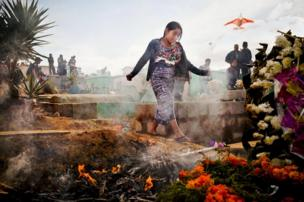 شابة تجوب بين شواهد القبور في مقبرة محلية احتفالا بيوم الموتى. وأطلقت الطائرات الورقية الملونة لتخويف الأرواح الشريرة حتى يتمكن الموتى من التمتع بزيارة أقاربهم