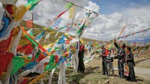 Creyentes budistas colgando banderas de oración en un cruce montañoso