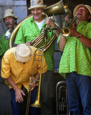Los músicos de una banda de vientos, con sus instrumentos y camisas coloridas, estallan en carcajada