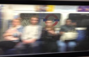 People sit on an underground carriage as it moves