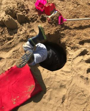Boy in a hole on the beach