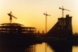 Three crane symmetry under construction at sunset