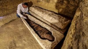 أثري مصري يفحص مومياء