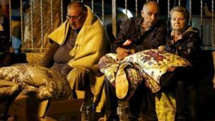Tres personas tapadas con mantas en la calle.