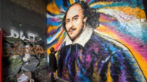 Graffiti artist James Cochran, aka Jimmy C, works on his mural of William Shakespeare on Clink Street, near the Shakespeare's Globe theatre in London