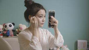 Lele Tao puts on make-up up in her night gown.