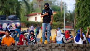 A young man, holding his homemade mortar, stands atop a makeshift wall, flanked by a dozen others. All wear face coverings.