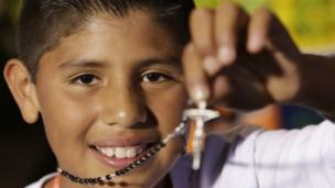 Brayan Fernandez, one of the children from the District's Institute for the Protection of Childhood and Youth, shows a rosary he was given by Pope Francis at the Papal Nunciature in Bogotá, Colombia, 6 September