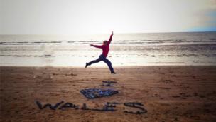 Mel Garside jumping on the beach