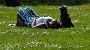 A woman and her dog lying in the park