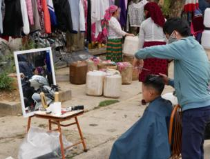 A young boy looks at his reflection as he has his hair cut in a makeshift salon on the street