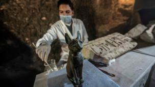 An Egyptian archaeologist cleans the bronze ancient Egyptian sitting cat statue. 10 Nov 2018