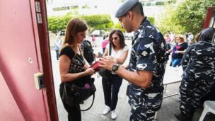 رجل أمن يفحص هوية إحدى الناخبات