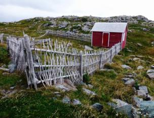A red hut and fence in a rocky landscape