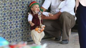 وإلى الشمال يوم الاثنين، كان هذا الطفل الصغير يبتسم قبل المشاركة في الاحتفال السنوي بالختان في مدينة القيروان بتونس.