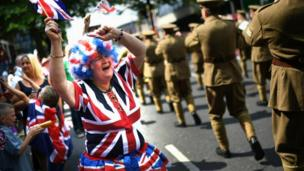 A woman is pictured wearing union jack attire with uniformed marchers in the foreground