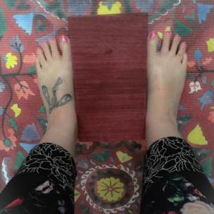 Pies sobre una alfombra de yoga