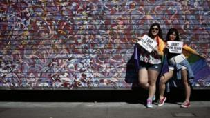 """Two women hold signs reading """"LGBT without Temer"""" at the Sao Paulo Gay Pride parade"""