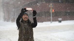 Seorang wanita tengah mengambil foto saat salju turun.