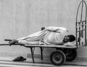 A man takes a nap on a trolley