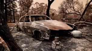 Um carro queimado por incêndios em Sarsfield, Austrália