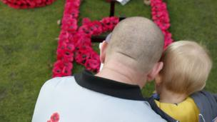 A man and a child look at a poppy display in the Remembrance Garden in Edinburgh