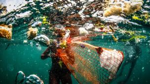 Imagen bajo agua de una persona que recoge plástico en el mar