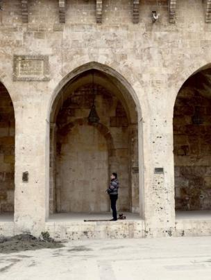 A man can be seen praying inside one of the arches of the mosque
