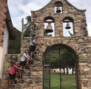 Tres jóvenes posan en orden ascendente de sus edades frente a un campanario