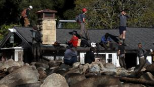 Rescuers on roof of house buried by mudslide in California. 10 Jan 2018