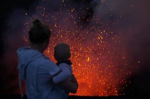 امرأ تحمل طفلة أمام بركان
