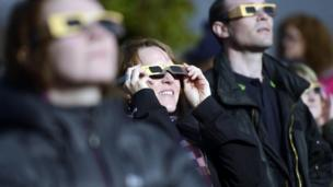 People looking at solar eclipse