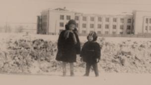 """Бывший заключенный колымских лагерей, в 1961 году """"не выездной"""" фотограф-любитель снимает своих детей на фоне здания, которое в годы сталинских репрессий занимала Центральная больница Управления Северо-Восточных Исправительно-трудовых Лагерей в поселке Дебин"""