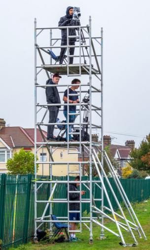 Camera men on different levels of scaffolding film a football match