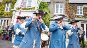 Members of a fife and drum band play their instruments on parade