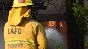 A firefighter douses flames in a California home.