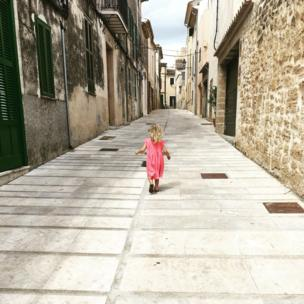 Girl in a pink dress in a Spanish street