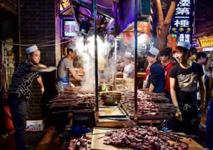 Street Vendors cook skewers of meat on a very busy street