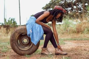 Woman sitting on a tyre